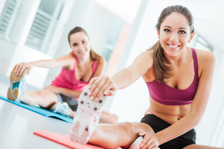 mat: Smiling young women at the gym doing a stretching exercise for legs on a mat, fitness and health concept
