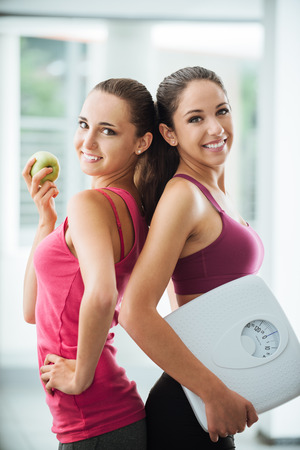 Happy teenage girl friends holding an apple and a scale, they are posing and smiling at camera, fitness and weight loss concept
