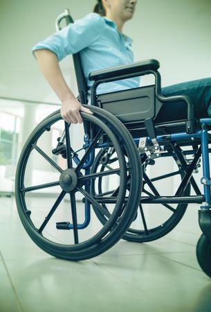 persona en silla de ruedas: Mujer joven en silla de ruedas que empuja manualmente en la rueda cerca, el concepto de discapacidad y minusvalía