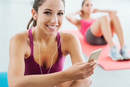 youth culture: Young smiling woman at the gym having a break and listening to music using a smart phone and earphones, fitness and youth concept