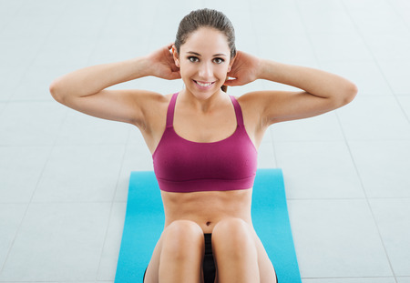 hands on head: Sporty young girl at the gym doing abdominals workout on a mat, she is smiling at camera, fitness and health concept