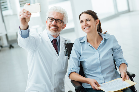 patient care: Smilng doctor taking selfies with a patient in wheelchair using a smart phone, care and disability integration concept