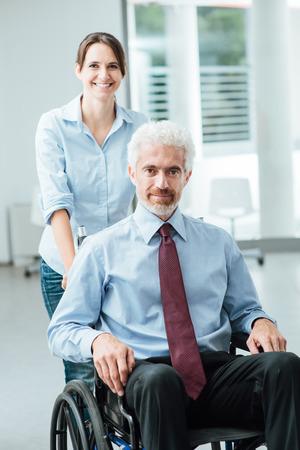 discapacidad: Mujer sonriente que empuja un hombre de negocios en silla de ruedas, la discapacidad y el concepto de la asistencia