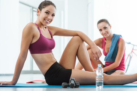 Beautiful young women at the gym sitting on a mat and having a break after exercising, they are smiling at camera, fitness and healthy lifestyle concept 版權商用圖片