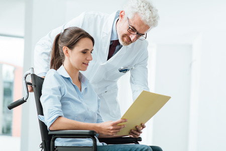 Doctor and patient examining a file with medical records, she is sitting on a wheelchair, assistance and health care concept