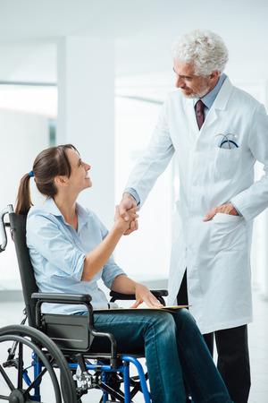 paraplegico: Confía médico sonriente agitando las manos con su nuevo paciente, ella es una mujer joven en silla de ruedas