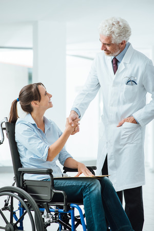 paraplegic: Confident smiling doctor shaking hands with his new patient, she is a young woman in wheelchair