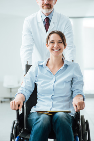 wheelchair woman: Doctor pushing a female patient in wheelchair, assistance and care concept