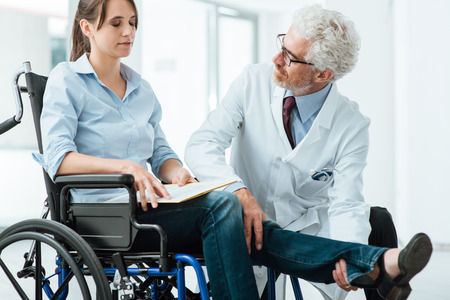Doctor visiting an invalid woman in wheelchair, he is examining her leg, rehabilitation and physioteraphy concept Stock Photo