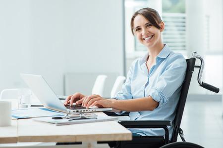 persona alegre: Confiado mujer de negocios feliz en la silla de ruedas de trabajo en el escritorio de oficina y con un ordenador portátil, ella está sonriendo a la cámara, el concepto de discapacidad superación