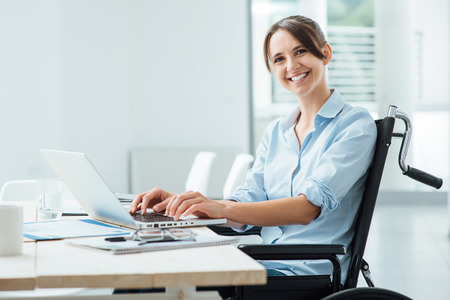 desk clerk: Confident happy businesswoman in wheelchair working at office desk and using a laptop, she is smiling at camera, disability overcoming concept