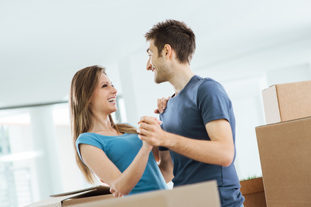 dancing house: Happy smiling couple dancing in their beautiful new house surrounded by carton boxes Stock Photo