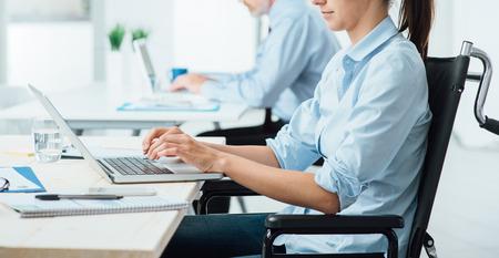 Jonge gehandicapte vrouw in een rolstoel werken op kantoor en het typen op een laptop, toegankelijkheid en onafhankelijkheid begrip
