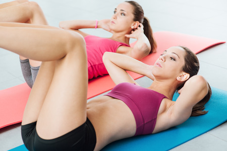gym workout: Young fit women at the gym doing abs workout on a mat, healthy lifestyle and fitness concept