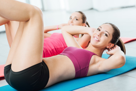 Sourire filles au gymnase faire des exercices abdominaux d'entraînement sur un tapis et regardant la caméra, le concept de remise en forme et de la formation