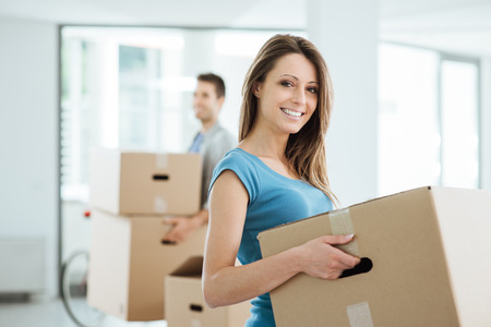 heavy lifting: Happy smiling couple moving in a new house and carrying carton boxes, relocation and renovation concept