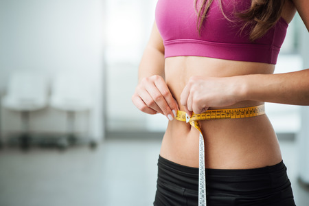 measure tape: Slim young woman measuring her thin waist with a tape measure, close up Stock Photo