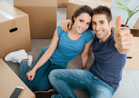 Happy young couple thumbs up and smiling at camera, they are sitting on their new house floor surrounded by carton boxes