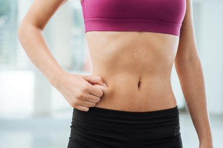 abdomen plano: Mujer joven delgada que pellizca la grasa en su vientre, la aptitud y la pérdida de peso concepto Foto de archivo
