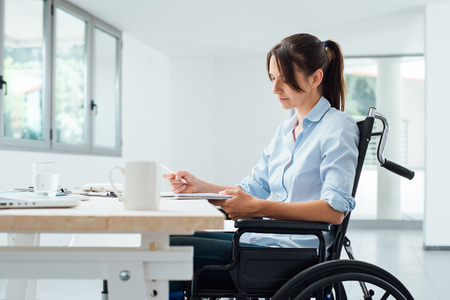 Confident disabled business woman in wheelchair working at office desk and checking paperwork 스톡 콘텐츠