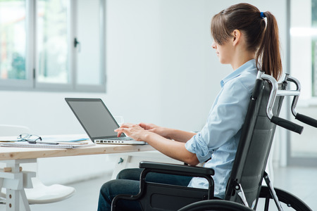 Young disabled business woman in wheelchair working at office desk and typing on a laptop, accessibility and independence concept