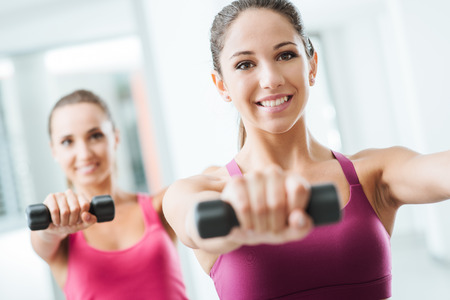 Teen sporty girls at gym exercising and weightlifting using dumbbells, body care and training concept Imagens