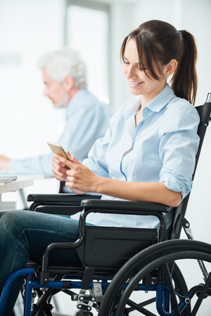 wheelchair woman: Confident business woman in wheelchair working at office desk and texting with her mobile phone, disability and employment concept