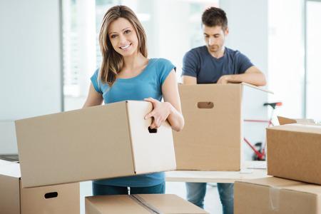 젊은 행복한 커플을 그들의 새로운 집에서 이동 상자를 풀고, 그녀는 판지 상자를 운반하고, 카메라에 미소