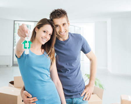 home keys: Young smiling couple holding their new house keys, real estate and relocation concept
