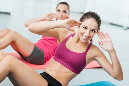 Lächelnde Frauen, die an der Gymnastik auf einer Matte und auf Kamera, Fitness- und Workout-Konzept