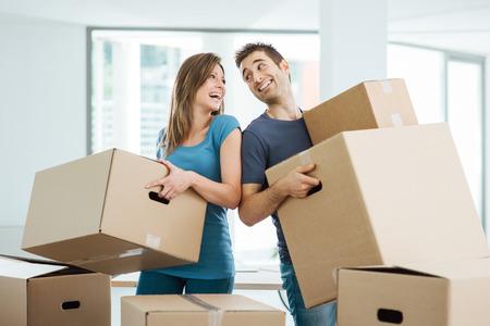 행복한 커플 서로 눈을 쳐다보고 그들의 새 집에 상자를 들고 스톡 콘텐츠
