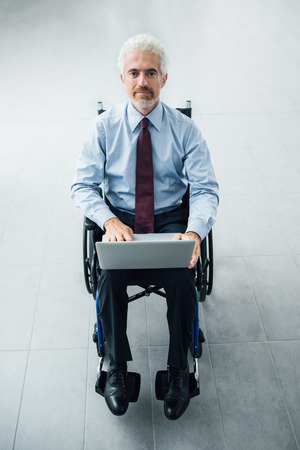 Confident smiling businessman in wheelchair using a laptop, office interior on background Imagens