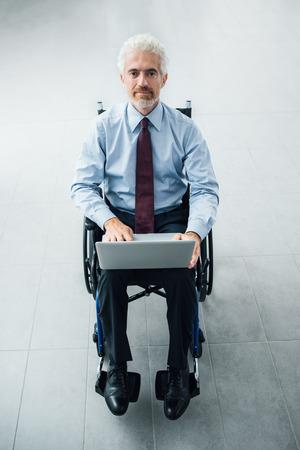 paraplegic: Hombre de negocios confidente sonriente en silla de ruedas con un ordenador portátil, interior de la oficina en el fondo