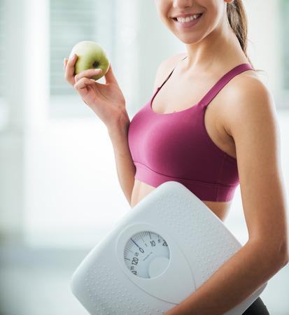 Usmívající se dospívající dívka drží váhu a čerstvé jablko, zdravé stravování, fitness a hubnutí koncepce Reklamní fotografie
