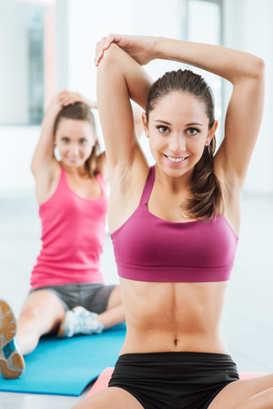 sports training: Young women at the gym sitting on a mat and doing stretching exercises for arms Stock Photo