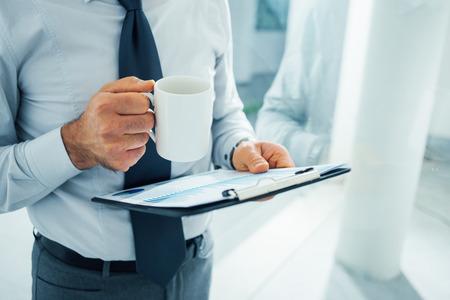 Executive werken tijdens zijn koffiepauze, wordt hij met een klembord en een mok met koffie