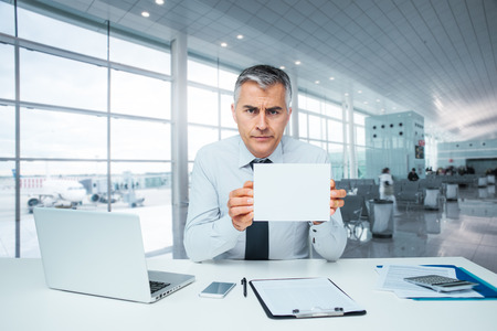Frowning bank clerk at desk holding a sign and rejecting a loan application Standard-Bild