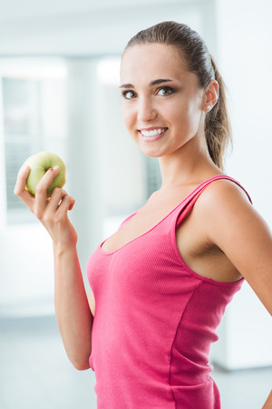 Young slim woman holding an apple and smiling at camera, healthy eating and weight loss concept photo