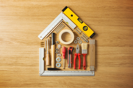Conceptual house composed of DIY and construction tools on hardwood flooring, top view Archivio Fotografico