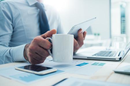 商人坐在辦公桌有一個休息時間,他手裡拿著一個杯子和一個數字平板電腦 版權商用圖片