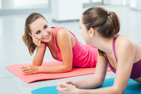 resting: Cute girls at the gym lying belly down on a mat, talking and gossiping