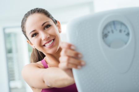 Boldog fiatal nő a fogyás, és bemutatja skálán, diéta és fitness koncepció