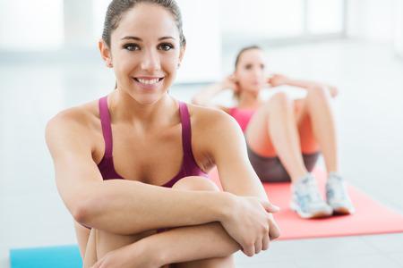Glimlachend tienermeisje in de sportschool met een pauze en zitten op een mat, een vrouw doet abs workout op de achtergrond, selectieve aandacht