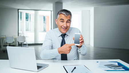 mobile technology: Smiling business man pointing at his smart phone and showing a mobile banking app Stock Photo
