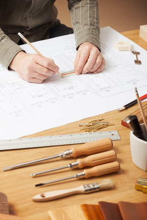 ruler: Professional architect and construction engineer working at office desk hands close-up, he is drawing on a building blueprint with a pencil and a ruler