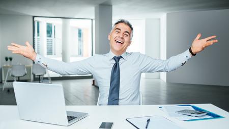 オフィス デスク、熱意、達成コンセプトでポーズ陽気な成功した実業家
