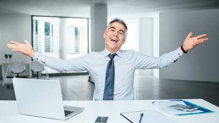 Cheerful successful businessman posing at office desk, enthusiasm and achievement concept Stockfoto