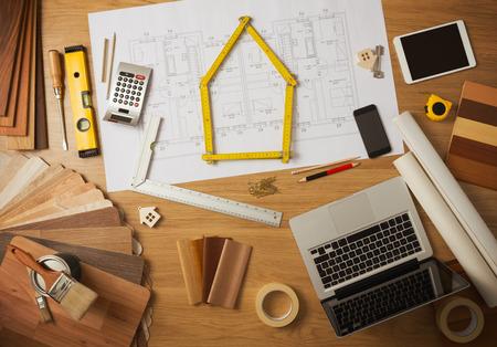 Építész és otthoni lakberendező asztali eszközök, laptop, fa színminták és home projekt tervezetét felülnézetből, a mérőket írása ház központban