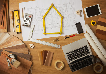 Architect and home interior decorator desktop with tools, laptop, wood swatches and home project draft top view, a meter is composing a house at center Stock fotó