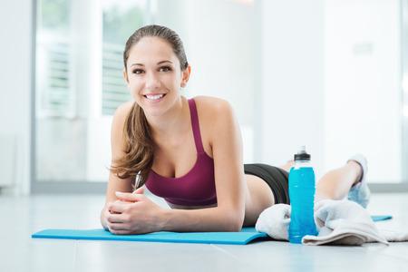 Lachende jonge vrouw ontspannen na de training, is ze rusten buik naar beneden op een mat en kijken naar de camera